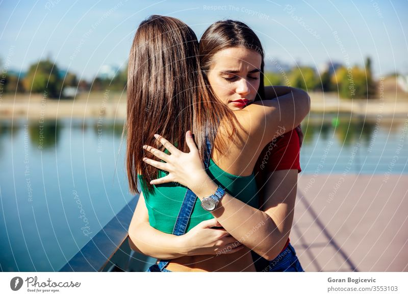 Young woman hugging and supporting her best female friend beautiful people water caucasian person young sadness loneliness pretty embrace nature love beauty