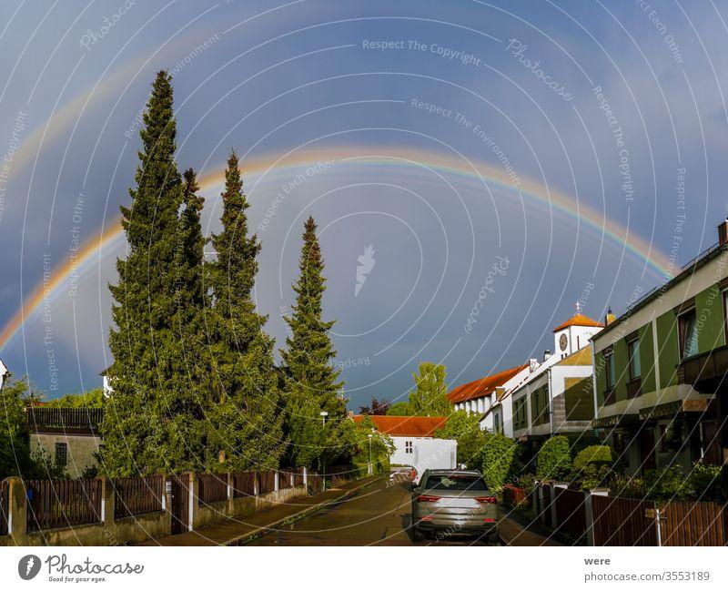 Rainbow over a residential area with church tower Drops Raindrops horizon landscape new beginning nobody rain sparkle sun sunlight sunshine thunderstorm