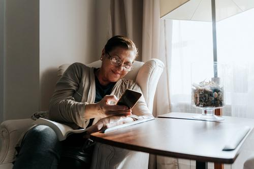 An older woman is sitting on the sofa with a book. She is typing on her phone while smiling. She is protecting herself and staying home. Pandemic concept.