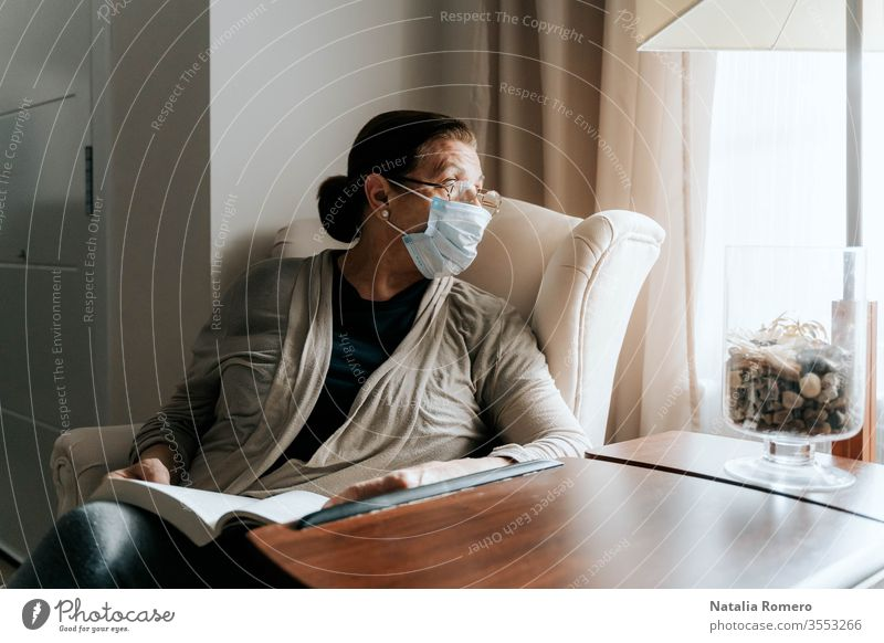 An older woman is sitting on the sofa with a book on her legs. She is looking through the window. She is sick and she is wearing a protective mask. She is protecting her family. Pandemic concept.