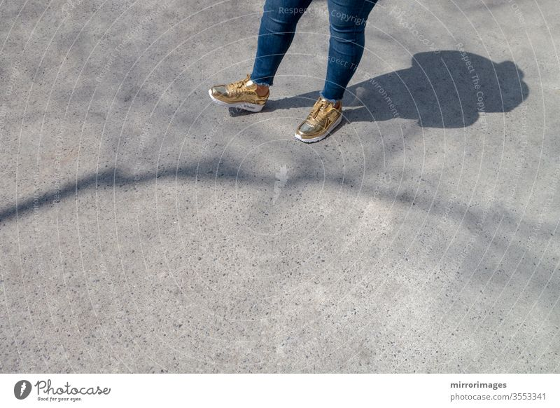 Chubby female wearing  tight blue jeans and golden white fashion sneakers waiting on a sidewalk with shadow and tree branch shadow slightly overweight woman