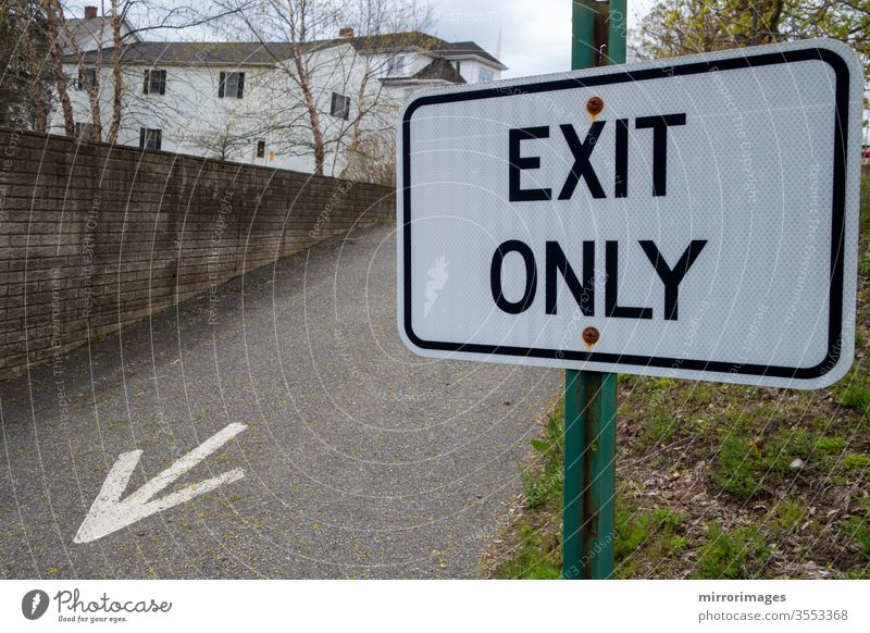 """Suburban area with exiting driveway with painted arrow on tarmac and green pole black and white sign reading """"Exit Only"""" reflective sign surface spring"""
