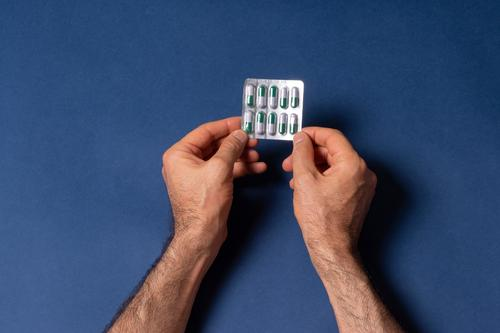 A man hands holding a small loaf of capsule pills in front of dark blue background single by fingers male people touch care treatment industry product human