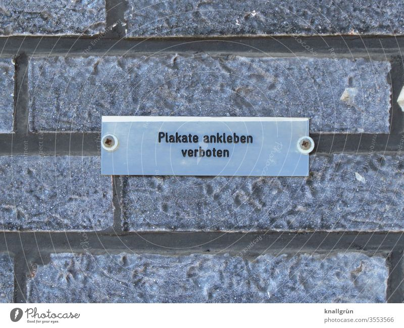 """Small screwed-on metal sign """"Posters are not allowed"""" on a grey clinker wall Signs and labeling Bans Communicate Signage Warning sign Exterior shot"""