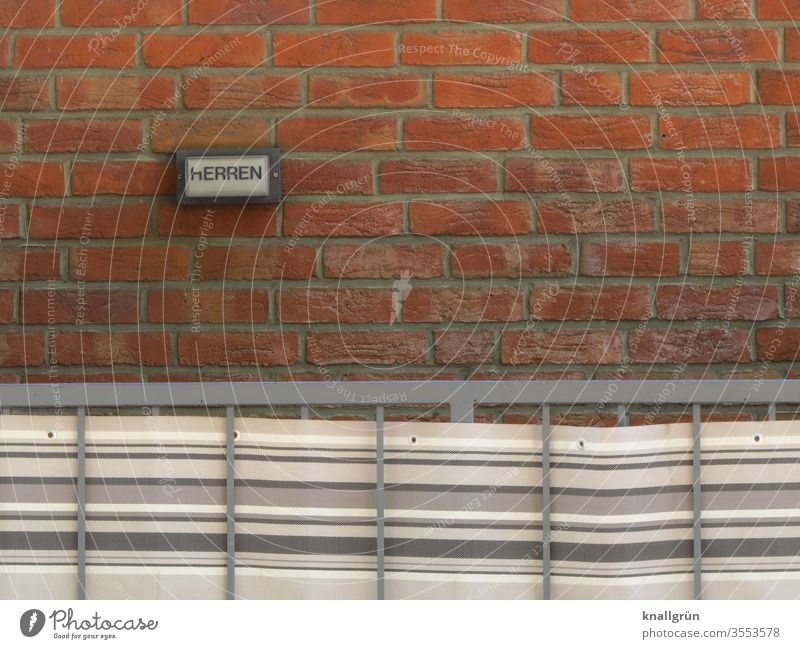 Small sign HERREN on red brick wall, in front of it a metal railing with striped awning fabric Signs and labeling Gentlemen's toilet Signage Exterior shot