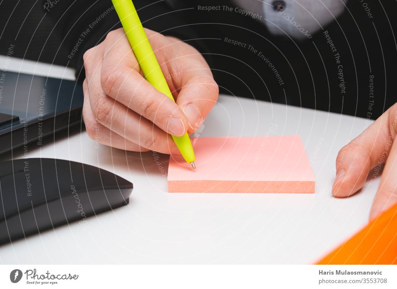 Hand writing with pen on the pink sticker note in the office close up adult background board building business closeup colors computer concept crayons design