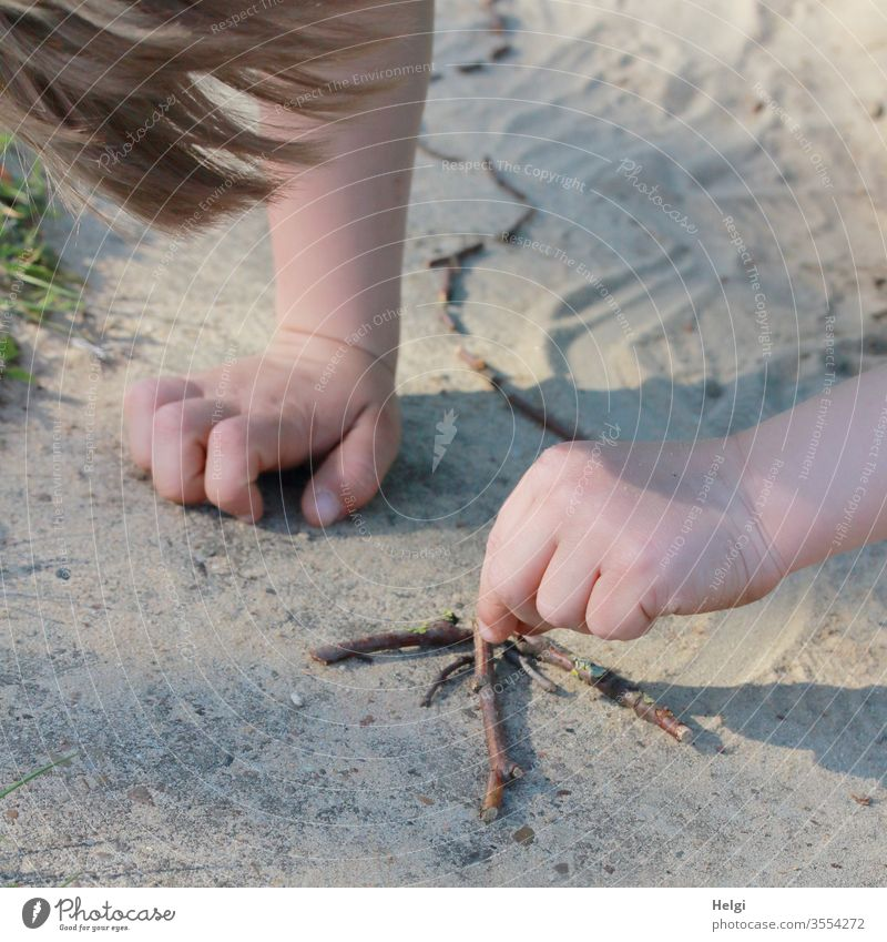 Living out creativity - close-up, little boy lays an arrow made of sticks in the sand Child Infancy Boy (child) Toddler Human being arm by hand hair Detail Sand