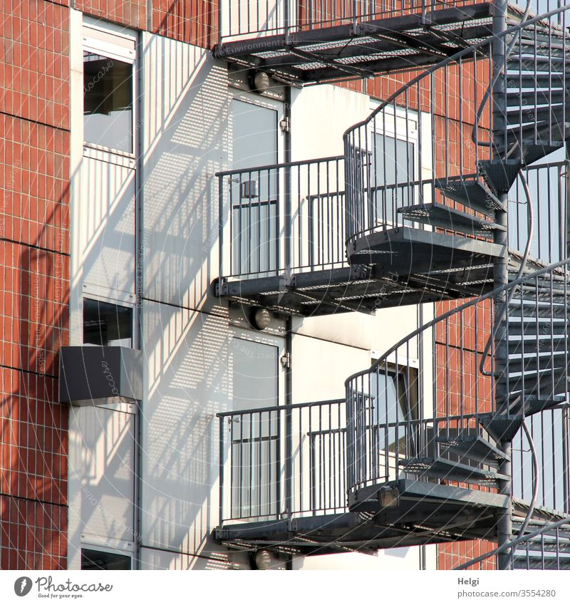 Metal staircase on a facade with light and shadow Facade Wall (building) Stairs Metal steps stair treads Handrail Window door Light Shadow Wall (barrier)