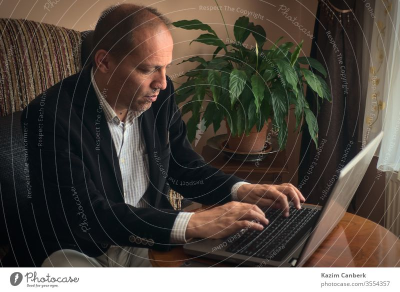 Serious adult male working from home typing by laptop with plant on backgroung work from home senior man telework computer online social life isolation distance