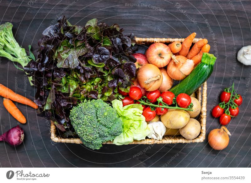 Fresh regional fruit and vegetable box on a brown wooden table, top view Vegetable Organic produce Vegetarian diet Nutrition Healthy Fruit- or Vegetable stall
