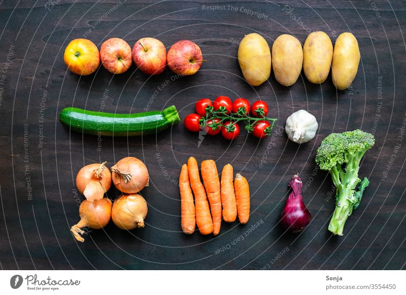 Fresh regional vegetables in a row on a brown wooden background, top view Vegetable variegated regionally vegetable box Food Organic produce Vegetarian diet