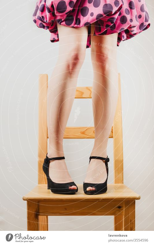Selective shot of white woman's legs in black high heeled shoes standing on a wooden chair. dressed up fun body faceless toned people lady person attractive