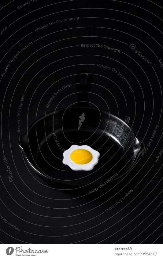 Black frying pan with egg inside on black background concept crockery dried empty food iron isolated kitchen minimalism mockup object slate white yolk