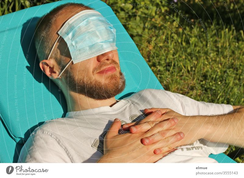 young man lies on a sun lounger and has a breathing mask in front of his eyes Respirator mask Face mask Eye protection hygiene sun protection Precuation peril