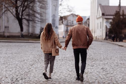 Love story of the beautiful young man and woman walking on the open air the city. embrace on a city walk. copy space. loving couple walking in the city in the open air
