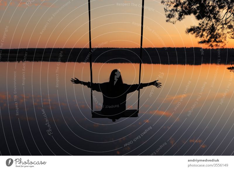 romantic young woman on a swing over lake at sunset. Young girl traveler sitting on the swing in beautiful nature, view on the lake sky water having fun playing