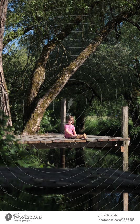 Toddler sitting on a catwalk between trees Footbridge Saale Franconia wood Willow tree River Plant Nature Water Wooden boards girl Sit leaves Gorgeous natural