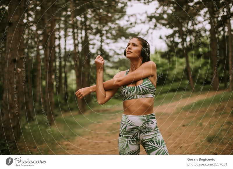 Young woman stretching and breathing fresh air in middle of forest while exercising young exercise fitness lifestyle workout healthy person adult female sporty