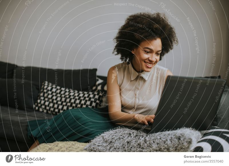 Attractive young woman working on laptop at home female computer people professional person business one technology african using internet curly black sitting