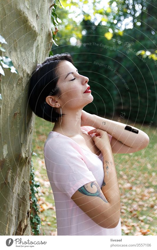woman charging batteries in the middle of nature girl tattoo recharging style reload tree greeny nice beauty cool hipster cute dark hair young lifestyle people