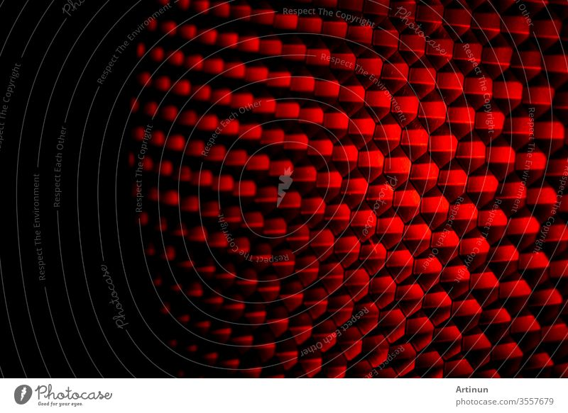 Closeup honeycomb grid texture with red light. Red and dark metal hexagon shaped pattern abstract background. Light modifier equipment. Metal honeycomb. Futuristic pattern. Honey grid cells network.