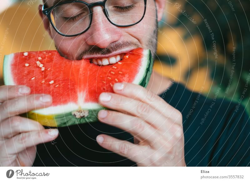 A man bites into a piece of watermelon Water melon bite into Bite Delicious Eating smile salubriously Fruity Man Joy feast fruit Juicy nib Nutrition Red Healthy