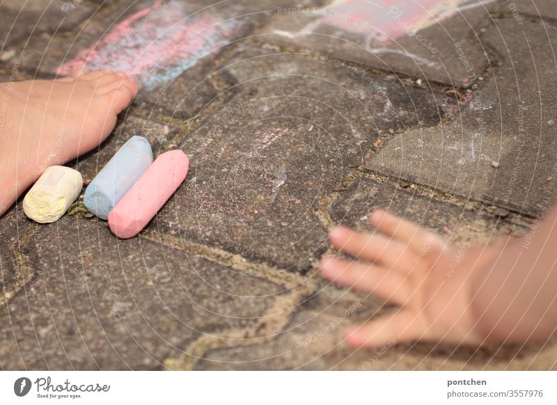 Two children paint with street chalk. Children's hand and foot game Painting (action, artwork) creatively feet hsbd variegated colors Creativity Infancy