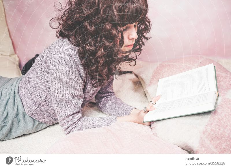 Young brunette woman reading a book in her bedroom student tired relax learn study home at home enjoy culture leisure pretty pink cute beautiful beautiful woman