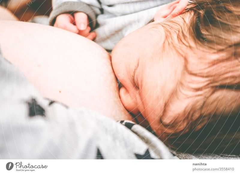 Close up of a young mother breastfeeding her little baby breast-feeding mom motherhood new born birth food eat eating head closeup close-up health healthy life
