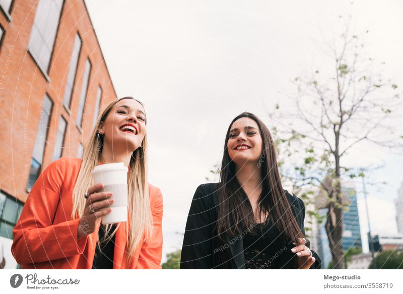 Two young friends walking together outdoors. two street city smiling pretty talking girlfriend town concept view style travel weekend looking enjoyment outside