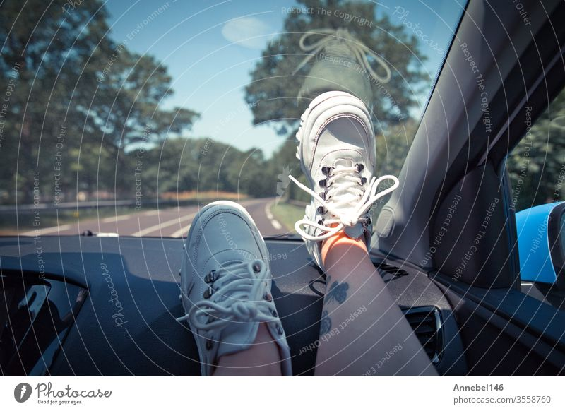 Freedom car travel concept - woman relaxing with feet on dashboard wearing white sneakers. Sexy woman in the car. background fashion tree person girl couple