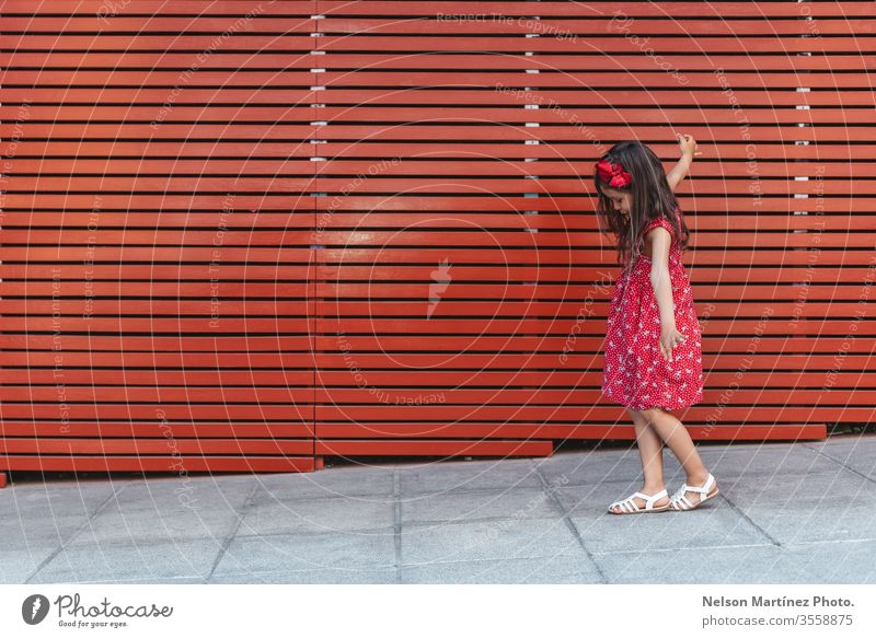 Happy little girl with arms wide open in front of a red background, wearing a red dress. summer fun cute kid funny happy hispanic childhood happiness portrait