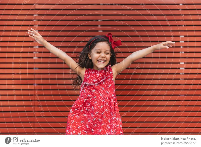 Happy little girl with arms wide open in front of a red background, wearing a red dress. summer fun cute kid funny happy hispanic child childhood young