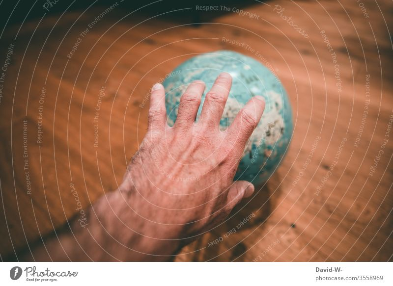 reach for the world - hand reaches for a globe by hand Grasp takes effect. Megalomania Globe Man corona improve Target Geography Around-the-world trip