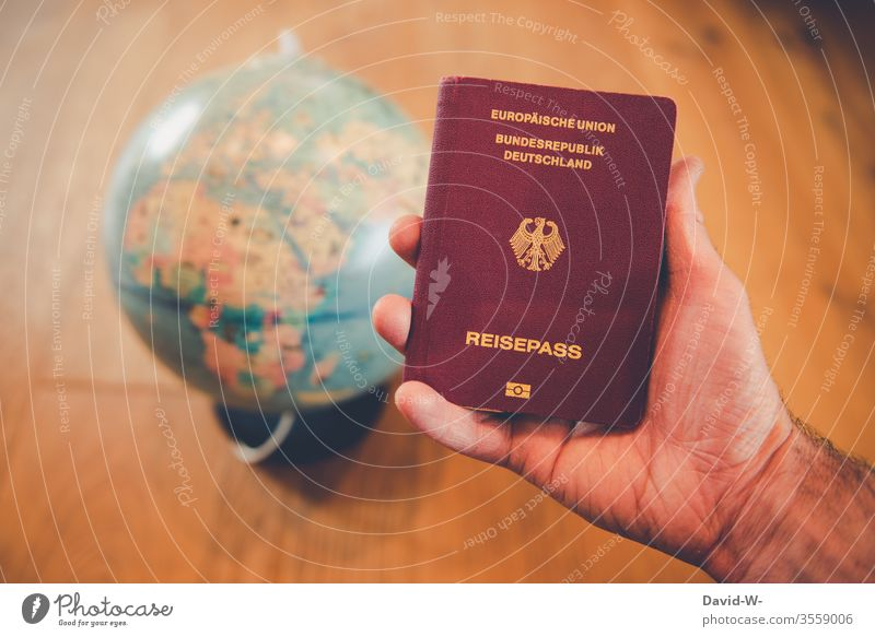 World trip - man holding passport in his hand with globe in the background Travel pass vacation Globe Around-the-world trip go away Man by hand Human being