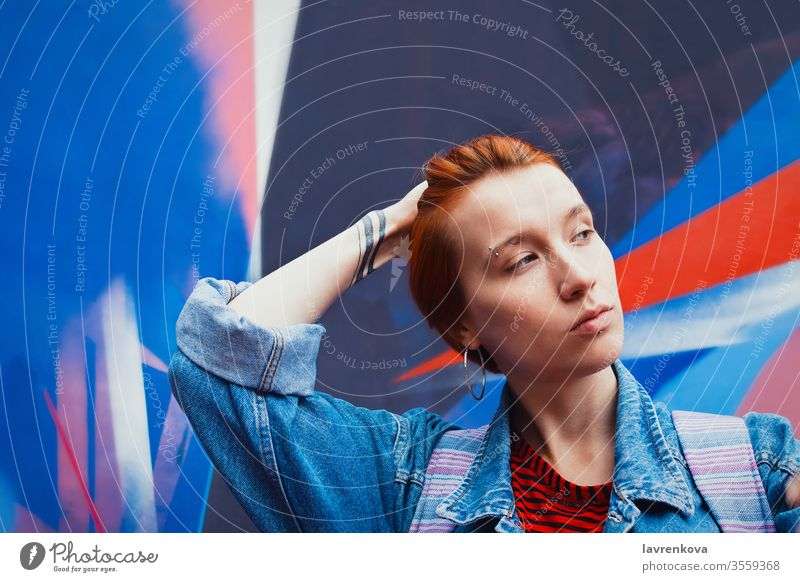 Young adult white woman in jeans jacket with died red hair flattens her hair down, lifestyle portrait with selective focus model street vacation female dyed
