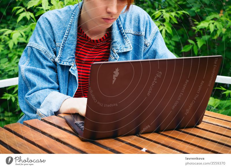 Closeup portrait of young adult female freelancer working on her laptop outside student online job sitting woman outdoor internet communication person lifestyle