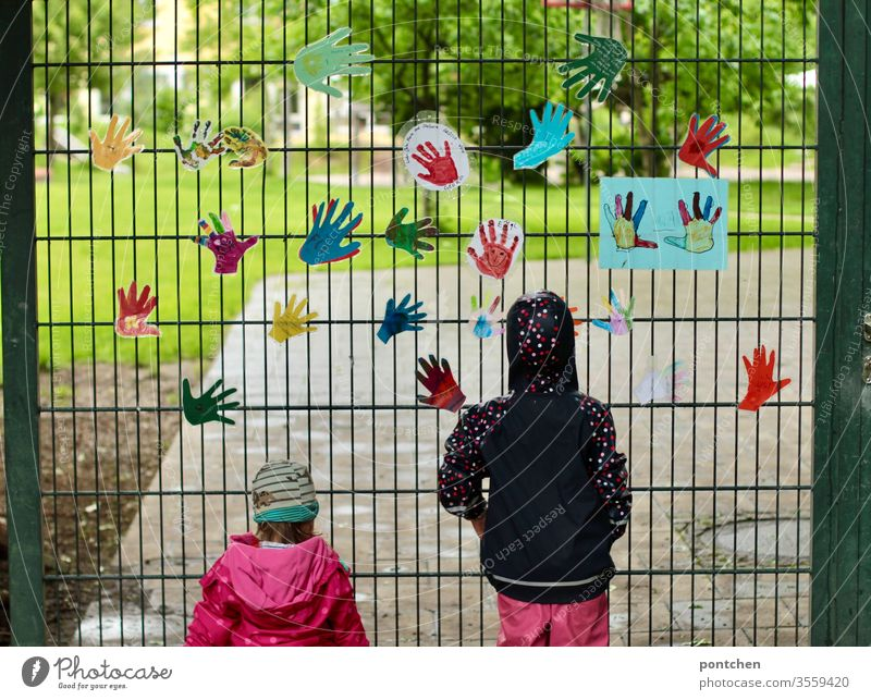 Two small female children in rainwear stand in front of the garden gate of a kindergarten and look inside. Colourful handicrafts hang from the gate. Longing, missing. Closure