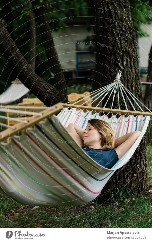 Young woman relaxing in the hammock in nature adult alone backyard calm carefree casual comfortable countryside day dream easy enjoy female forest furniture