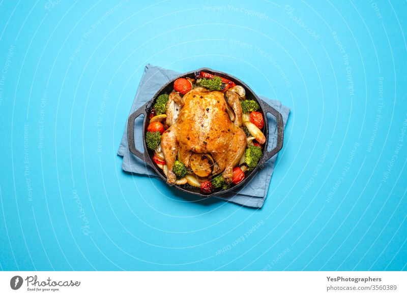 Roasted chicken with vegetables in an iron cast, top view. above view baked blue background broccoli christmas cook cooked copy space crispy cuisine diet dinner