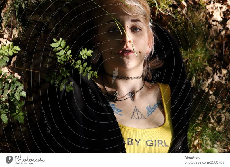 Portrait of a young woman with piercings, tattoos and tunnel, lying on the forest floor portrait Woman girl Blonde Piercing Jewellery Assecoires shirt Shirt