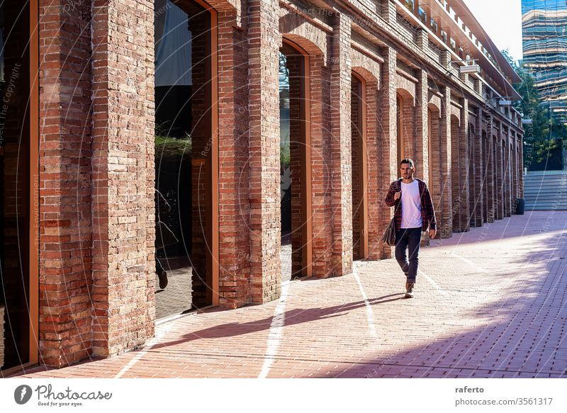 Bearded young male holding shoulder bag while walking in a business district adult man young adult outdoors people businessman beard portrait city one person