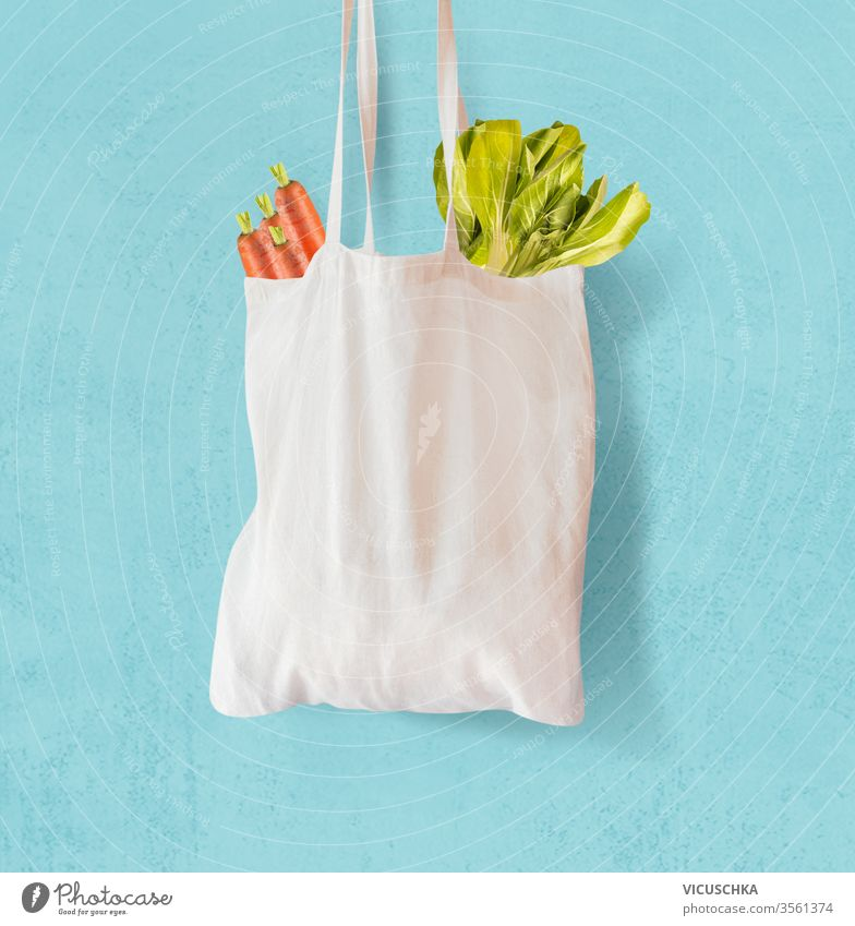 White  textile grocery shopping bag with vegetables hanging at light blue background. Zero waste concept. Cotton reusable bag. Plastic free shopping. Eco friendly bag mock up.