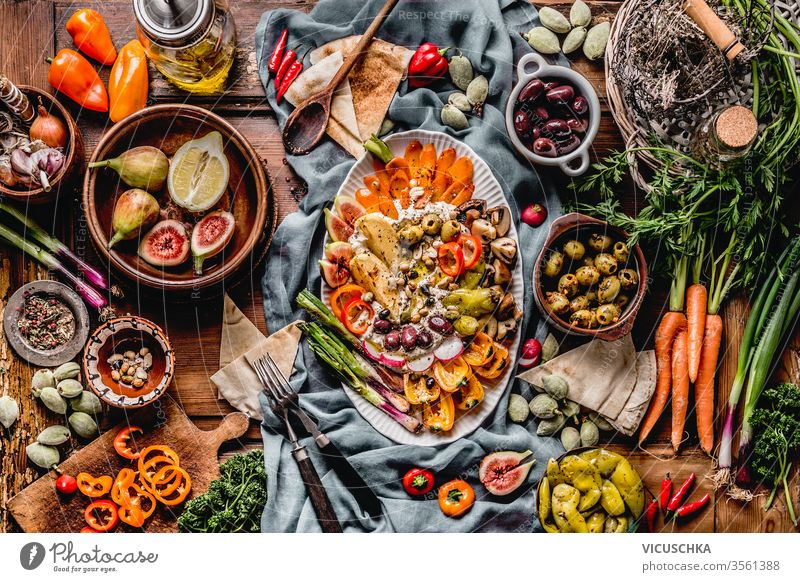 Tasty Mediterranean cuisine with hummus plate. Ramadan iftar dinner. Various pickled and fresh  vegetables: olives, fids, green almond. Vegan party food . Festive gathering