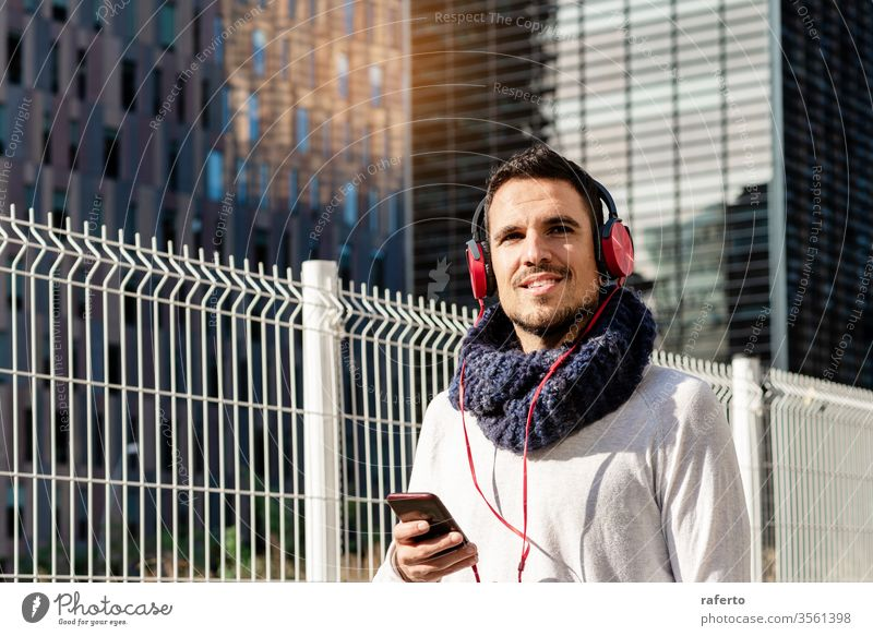 Young bearded male with headphones and holding smartphone while walking against skyscrapers in sunny day person man street outdoor earphones adult city