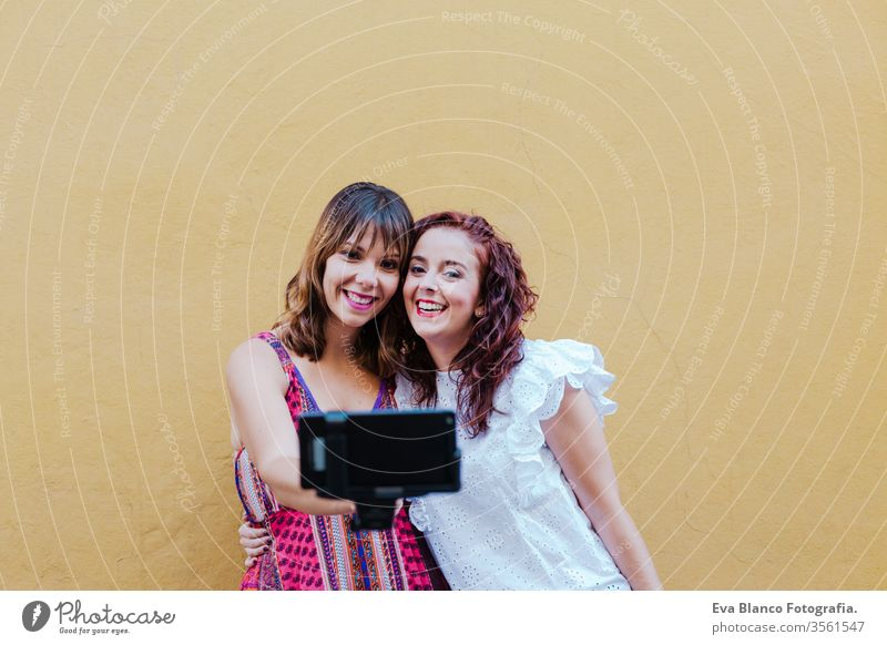 two friends or sisters taking a picture outdoors with mobile phone over yellow background. technology and lifestyle concept selfie city urban fun stick smiling