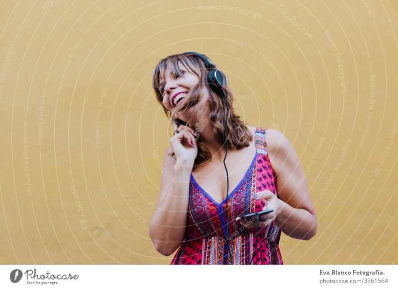 portrait of young caucasian woman outdoors over yellow background listening to music on headset and mobile phone. summer time technology app song people