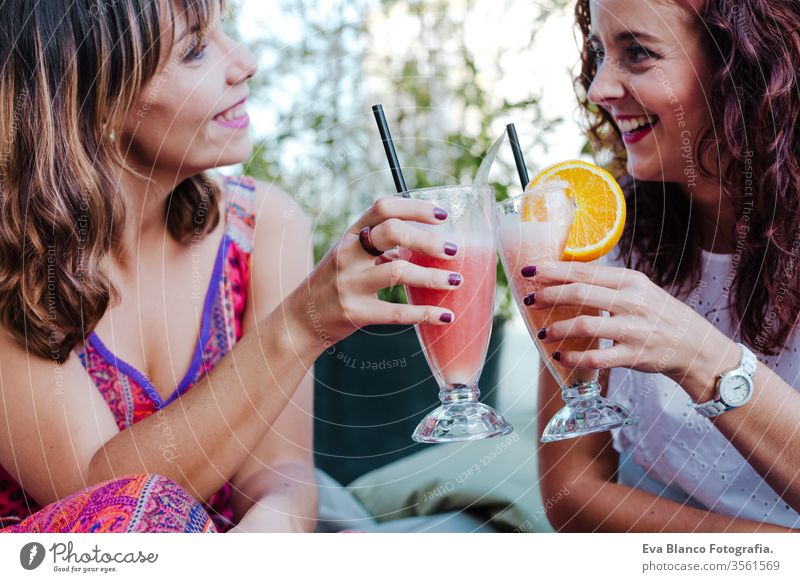 two friends enjoying a healthy smoothie in a terrace. summer time and friendship women happy juice fruit iced green sweet caffeine natural drink beverage