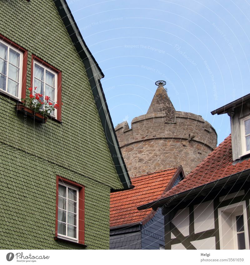 historical buildings with shingles, half-timbered and in the background a round tower in front of a blue sky built Manmade structures Facade wooden shingles