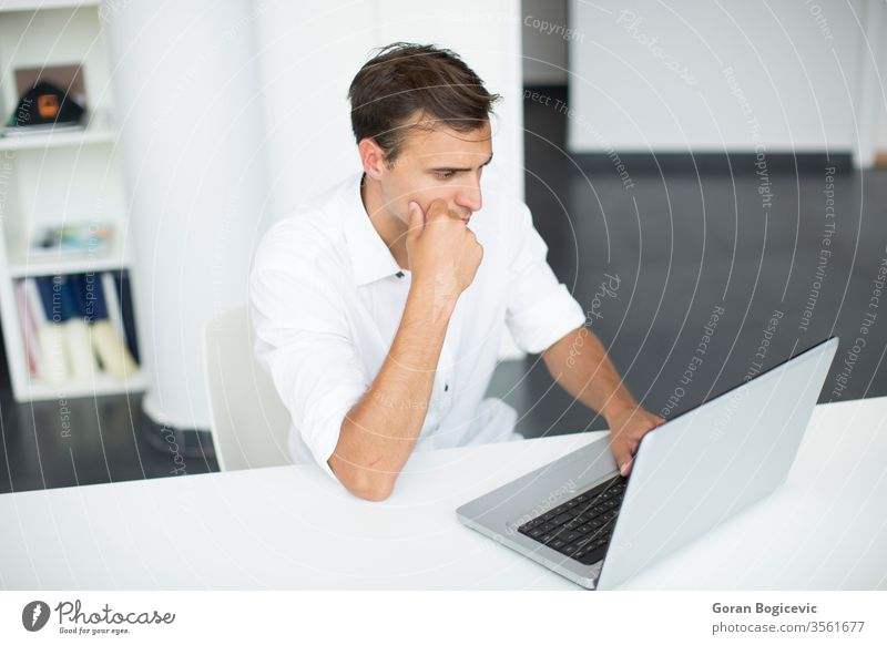Young man in the office business desk laptop looking handsome corporation issue white sitting adult copyspace determined occupation light involved one caucasian
